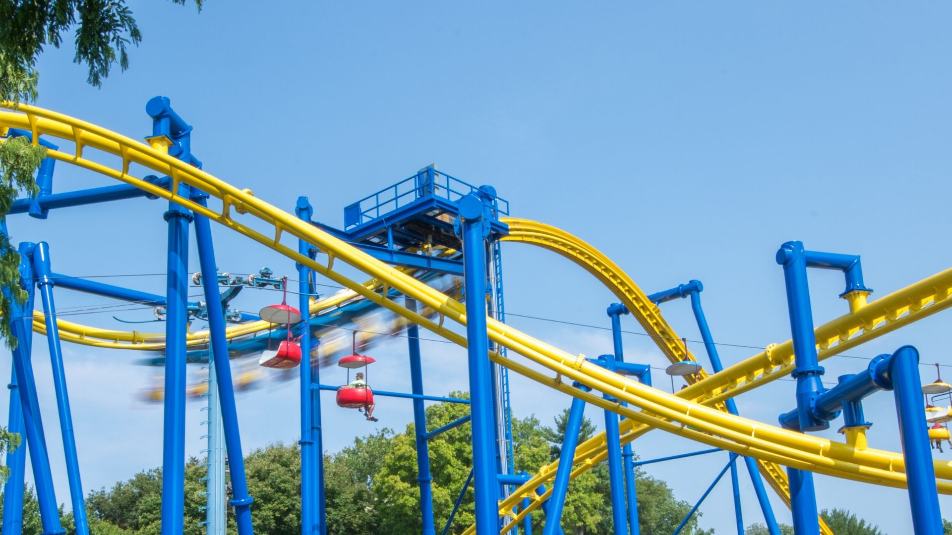Wide photo of yellow and blue roller coaster with sky ride gondolas passing below it