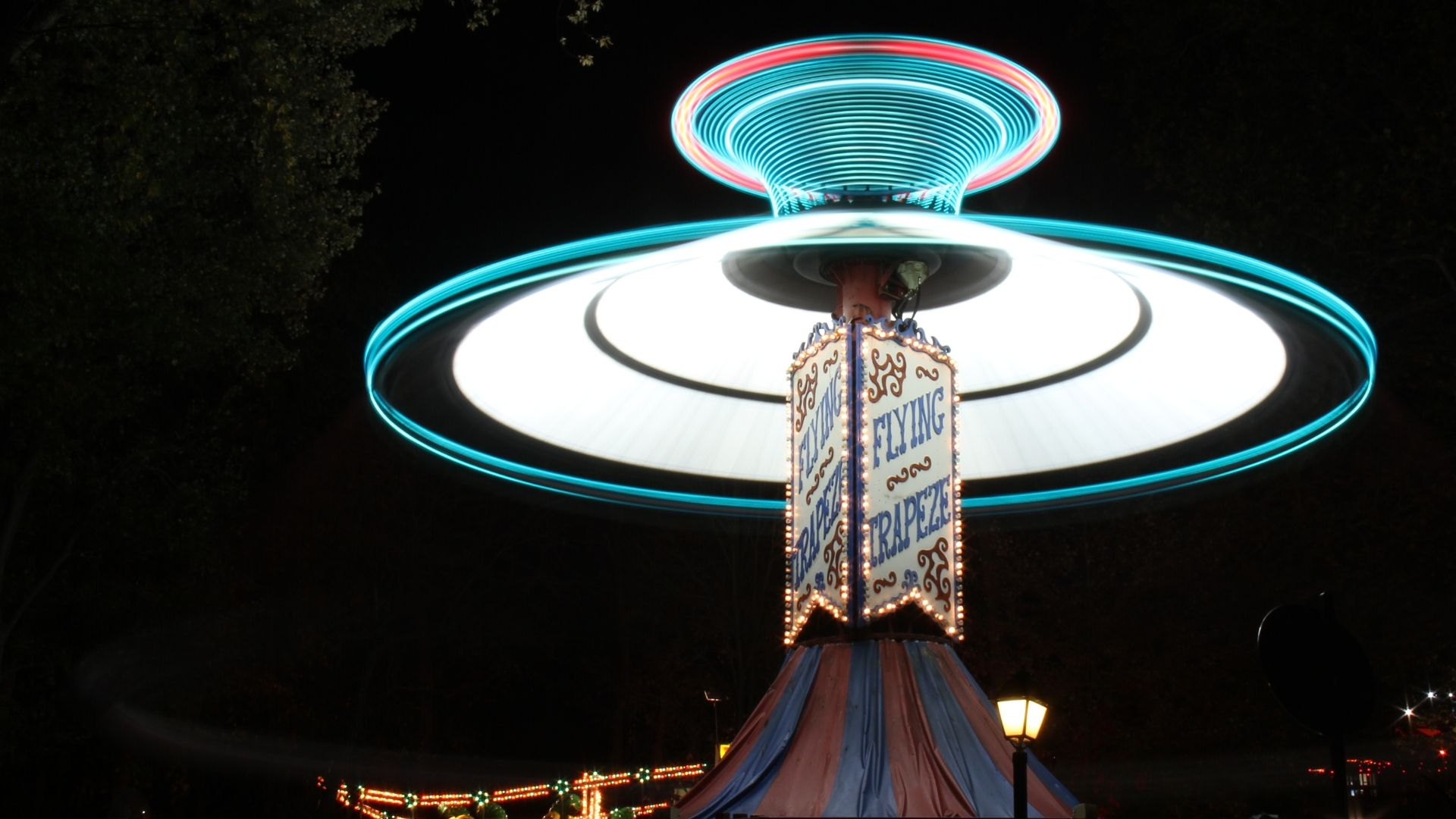 Long exposure photo with spinning Trapeze ride producing circular light trails at night