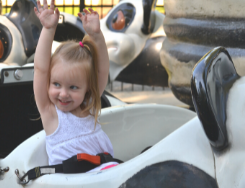Little girl with her hands up laughing on a ride