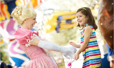 Princess in pink dress playing with young girl in multicolored striped dress