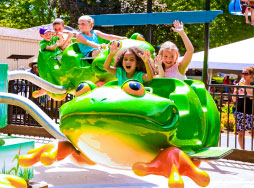 Children laughing with arms raised in the air on a green, frog-shaped ride vehicle.