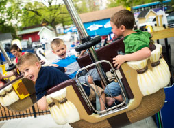 Three boys smiling while riding in balloon basket ride vehicle