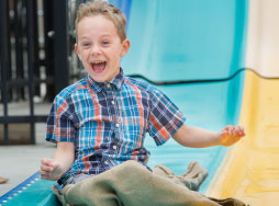 Young boy smiling as he slides down large multi-colored slide.