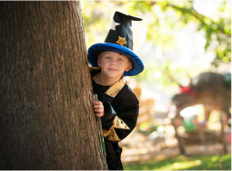 Boy dressed in wizard costume behind a tree