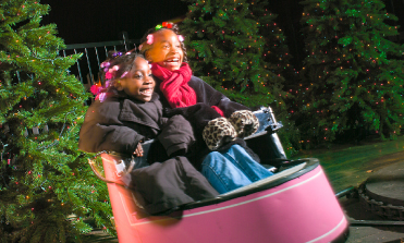 Two girls in winter coats riding the Wonder Whip attraction at Dutch Wonderland