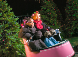 Two girls in winter coats riding the Wonder Whip attraction
