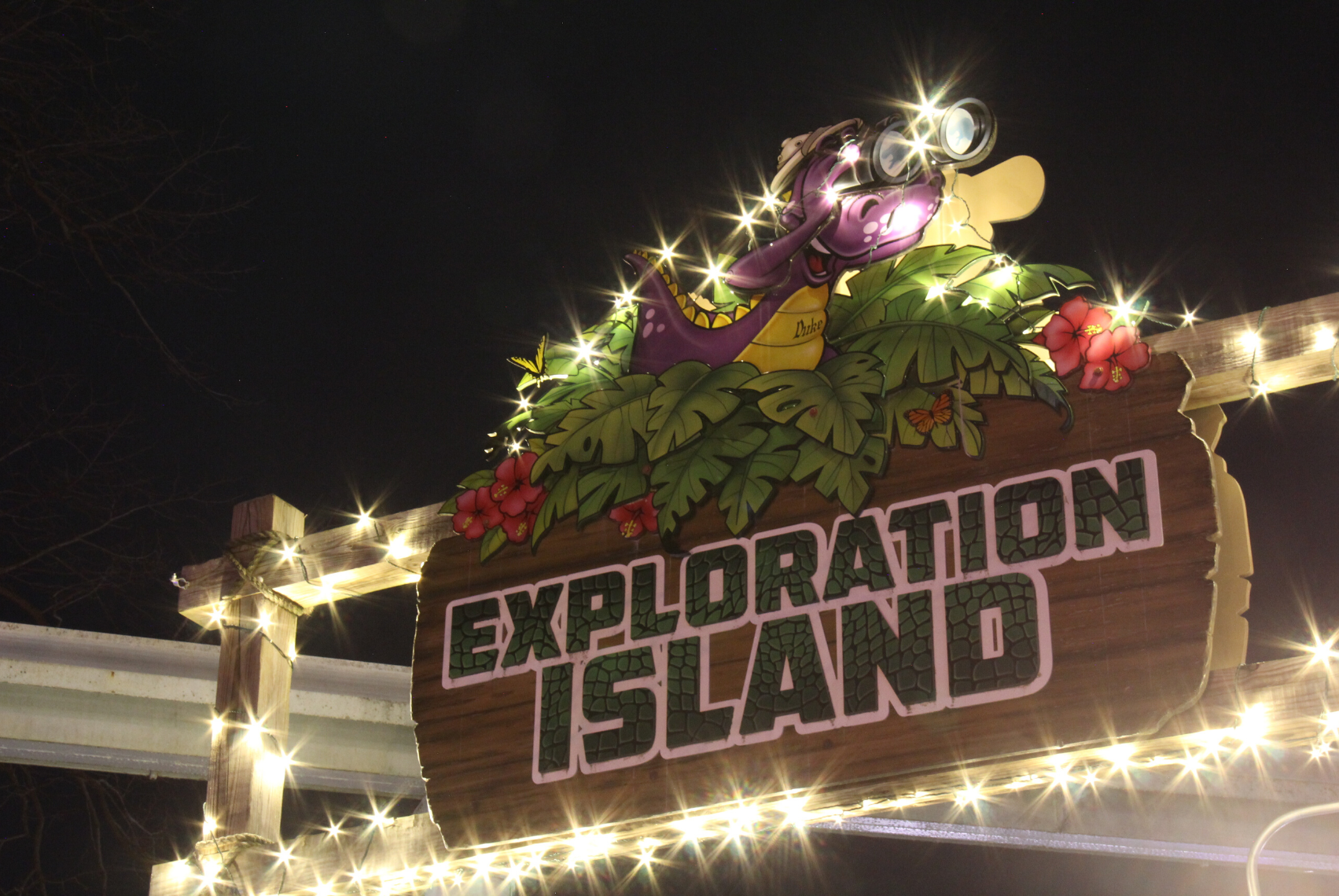Exploration Island sign covered in white holiday lights