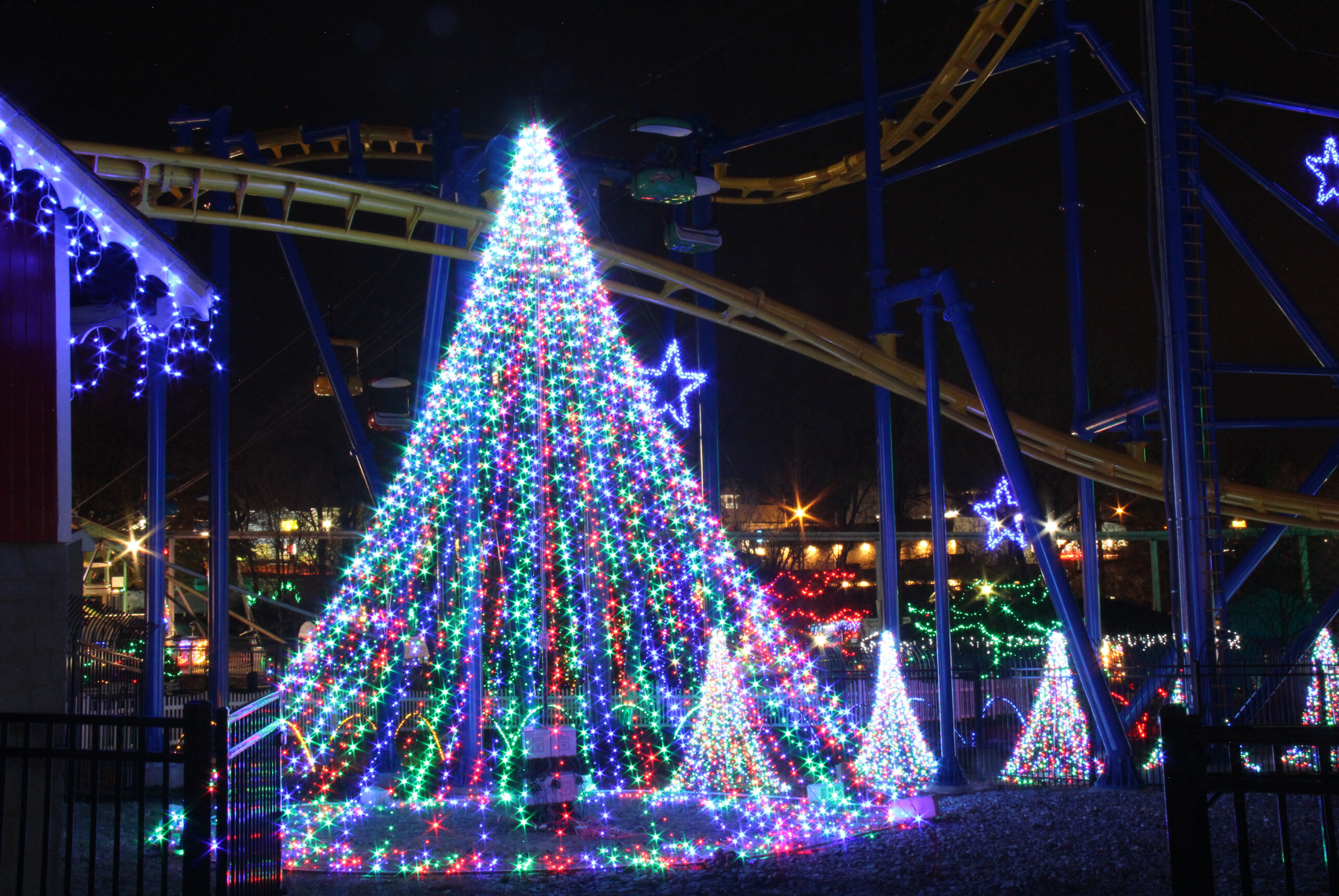 Trees made of holiday lights in front of Merlin's Mayhem Family Roller Coaster