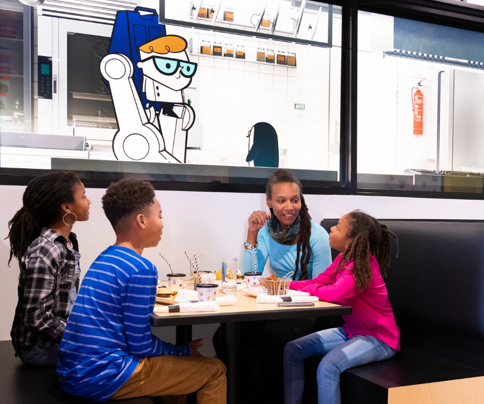 Family eating in front of digital screens of cartoon characters cooking