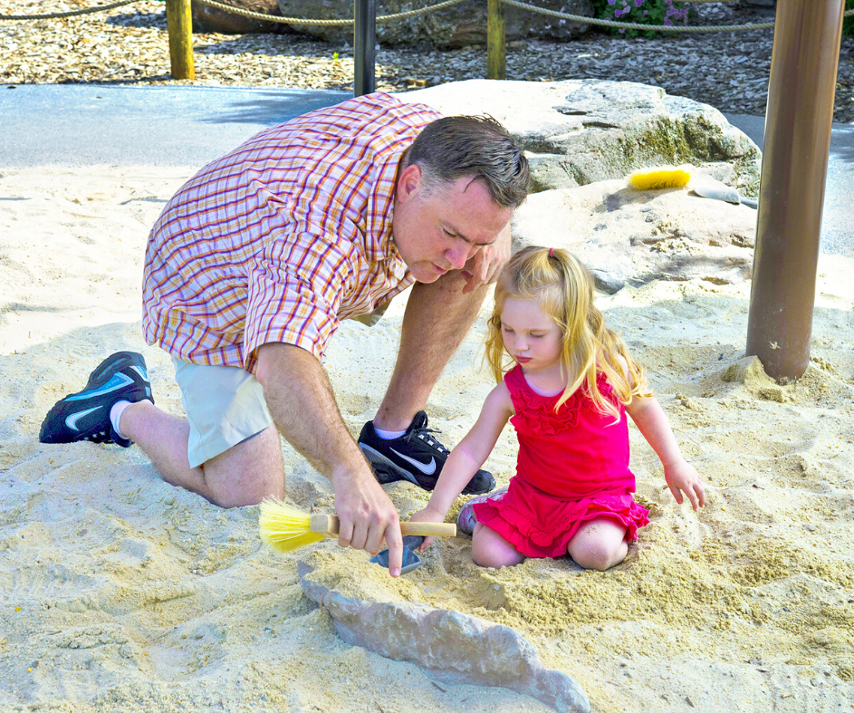 Man and girl digging in Dino Dig attraction