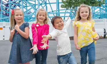 Four children smiling with outstretched arms standing in front of a roller coaster