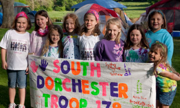 Group of Girl Scouts holding troop sign