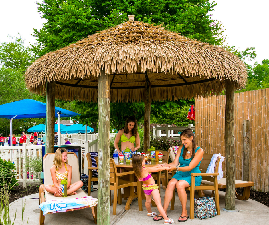 Two women and two girls sitting and interacting with each other in a cabana