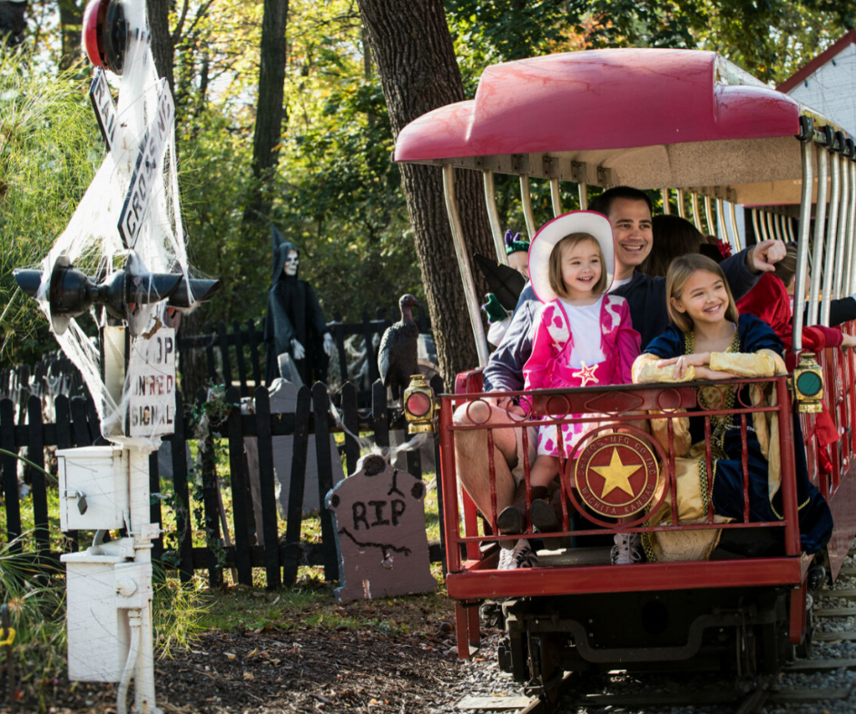 Family in Halloween costumes riding the train