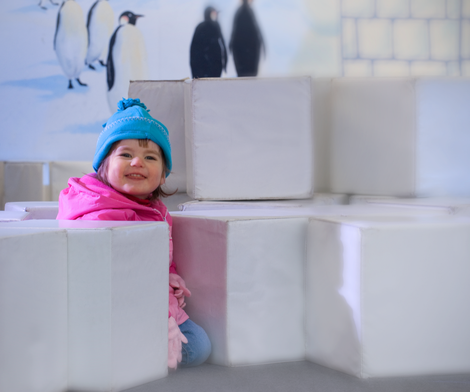 Girl sitting with large foam ice blocks in Polar Playground