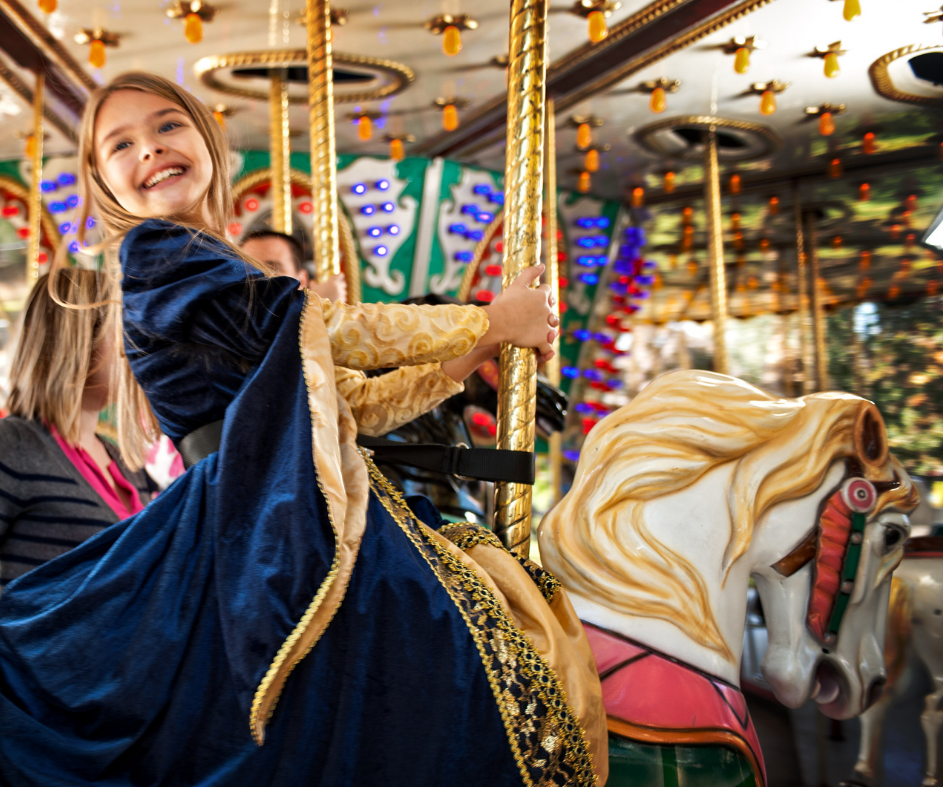 Girl in navy dress sitting on a carousel horse