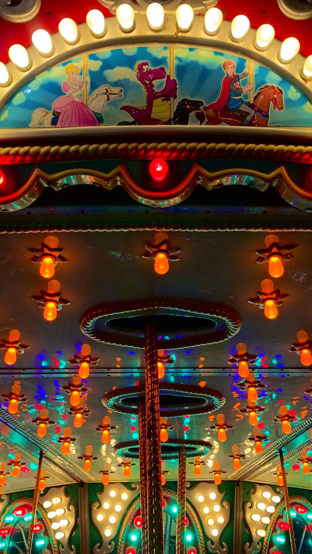 Close-up photo of a merry go round lit up at night