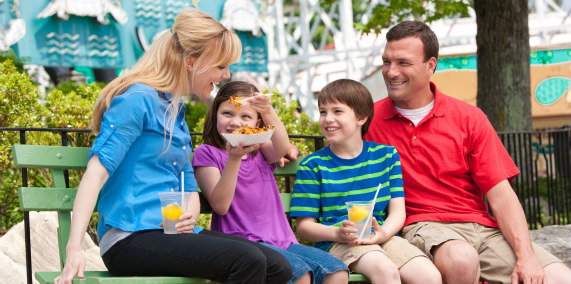 Family enjoying Potato Patch french fries while sitting on a bench