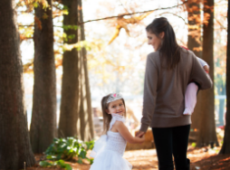 Little girl wearing a white princess dress and tiara is walking hand-in-hand with mom in a colorful tree enclosure during fall.