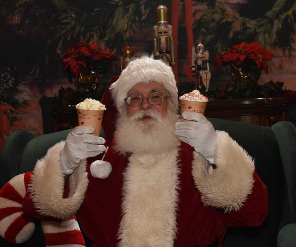 Santa Claus holding two cups of hot cocoa