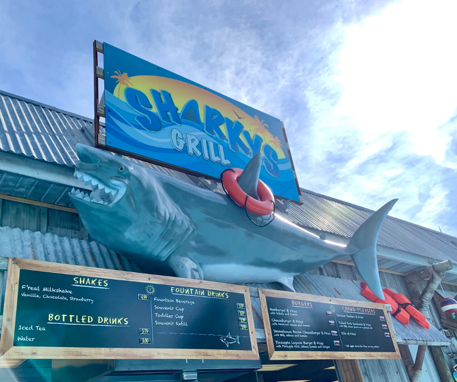 Front of Sharkys Grill restaurant. A shark sculpture and menu signs are featured