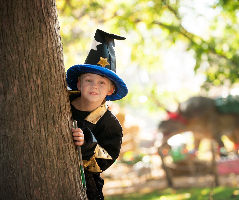 Wizard dressed child peaking out behind a tree on Exploration Island