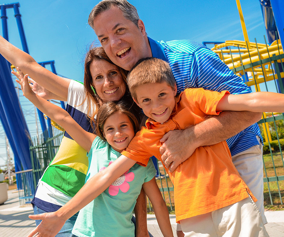 Smiling family in front of roller coaster